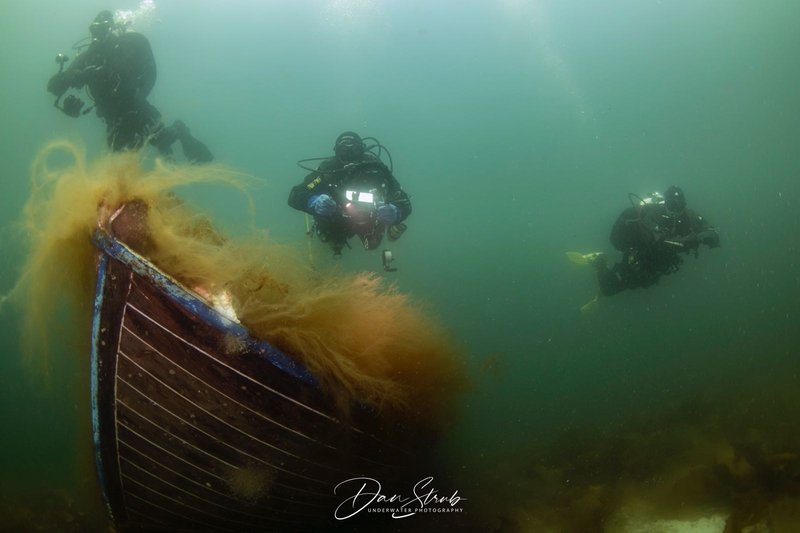 Different divers diving over a wreck